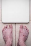 Ugly feet and scale. Ugly feet getting ready to step on a bathroom scale stock photography