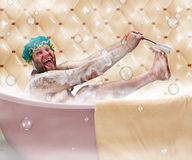 Ugly man in bath. Bizarre ugly man washing his leg in a bath stock images