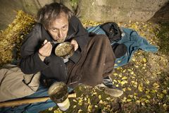 Poor unemployed man on backstreet yard place eating lentil soup. Ugly pauper man living outdoor preparing and eating lentil soup stock image