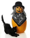 Ugly Pumpkin with Halloween Cat. A Halloween cat by a 2-tier happy, ugly pumpkin man with stringy gray hair and a top hat.  On a white background Royalty Free Stock Photo