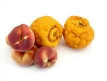 Ugly tangerines and peaches. A couple ugly tangerines and a few donut peaches Stock Photos