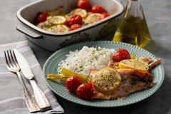 Ugnen bakade laxen med purjolöken och tomater som tjänades som med kokta ris arkivbild