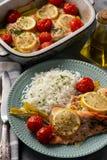 Ugnen bakade laxen med purjolöken och tomater som tjänades som med kokta ris fotografering för bildbyråer