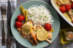 Ugnen bakade laxen med purjolöken och tomater som tjänades som med kokta ris royaltyfri foto