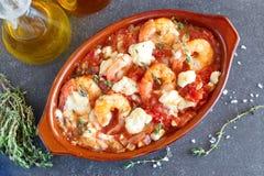 Ugnen drog tillbaka räkor med feta, tomaten, paprika, timjan i en traditionell keramisk form på en abstrakt bakgrund Sund ätaconc Arkivfoto