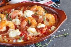 Ugnen drog tillbaka räkor med feta, tomaten, paprika, timjan i en traditionell keramisk form på en abstrakt bakgrund Sund ätaconc Royaltyfria Foton
