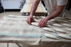 Ugniatający kawałki chleb nad fermentacja stołem i umieszczający Obraz Royalty Free