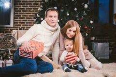 Uguagliare celebratorio di Natale della famiglia Gente caucasica della famiglia tre che si siede sotto l'albero di Natale della c immagini stock