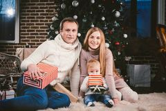 Uguagliare celebratorio di Natale della famiglia Gente caucasica della famiglia tre che si siede sotto l'albero di Natale della c fotografia stock libera da diritti