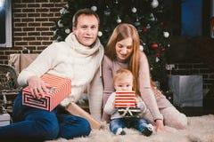Uguagliare celebratorio di Natale della famiglia Gente caucasica della famiglia tre che si siede sotto l'albero di Natale della c immagini stock libere da diritti