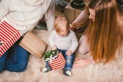 Uguagliare celebratorio di Natale della famiglia Gente caucasica della famiglia tre che si siede sotto l'albero di Natale della c fotografia stock