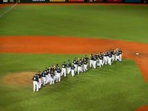 UH παίχτες του μπέιζμπολ υψηλός-πέντε μεταξύ τους στη μέση του τομέα στοκ φωτογραφίες