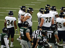 UH Football and UC Davis players standing after play during coll Stock Image