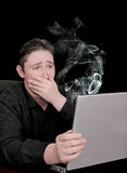 Uh oh computer. Man seeing computer smoke and die is very unhappy Stock Photos