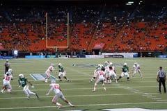 Uh-Quarterback stellt ein, um Ball zu werfen, während Spieler wühlen, um ope zu erhalten Stockbilder