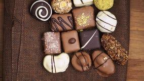 Ручной работы конфеты шоколада падая на деревянную предпосылку, вкусные помадки в замедленном движении видеоматериал