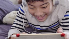 Asian cute boy watching on tablet computer and wearing white headphone with smile face. stock video