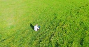 UHD 4K鸟瞰图 在商人的低轨道飞行坐与笔记本垫的绿草在领域 影视素材