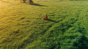 Low altitude radial flight over sport yoga man at perfect green grass. Sunset in mountain. UHD 4K aerial view. Low altitude radial flight over sport yoga man at stock video