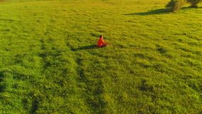 Low altitude radial flight over sport yoga man at perfect green grass. Sunset in mountain. UHD 4K aerial view. Low altitude radial flight over sport yoga man at stock footage