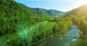 UHD 4K aerial view. Low flight over fresh cold mountain river, meadow and road at sunny summer morning. stock footage