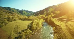 UHD 4K aerial view. Low flight over fresh cold mountain river, meadow and road at sunny summer morning. UHD 4K aerial view. Low flight over fresh cold mountain stock footage