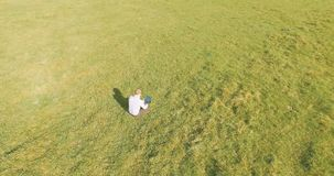UHD 4k aerial view. Low orbital flight over businessman sitting on green grass with notebook pad at field. UHD 4k aerial view. Low orbital flight over stock footage