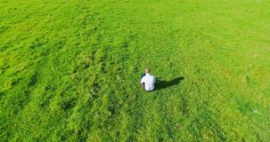 UHD 4k aerial view. Low orbital flight over businessman sitting on green grass with notebook pad at field. UHD 4k aerial view. Low orbital flight over stock video footage