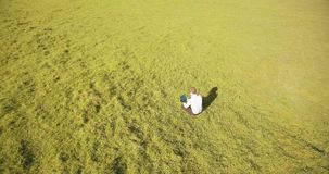 UHD 4k aerial view. Low orbital flight over businessman sitting on green grass with notebook pad at field. UHD 4k aerial view. Low orbital flight over stock video