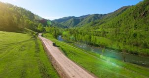 UHD 4K aerial of vehicle driving towards the sunrice. Mid-air shot suv car driving Stock Footage