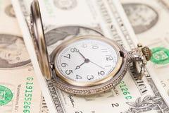 Uhr auf einem Haufen von Papierdollar Stockbild