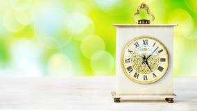 Uhr auf einem Holztisch Stockbilder