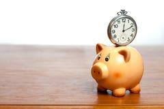 Uhr auf einem Sparschwein Stockfotografie