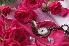 Uhr auf einer Kette unter den Rosen Stockfotografie