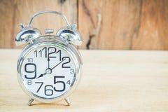 Uhr auf hölzernem Hintergrund Stockfotos