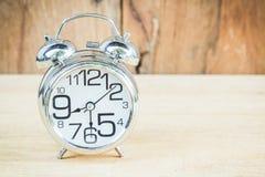 Uhr auf hölzernem Hintergrund Lizenzfreie Stockbilder