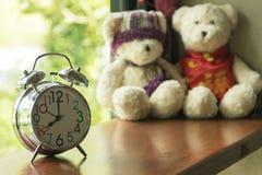 Uhr auf Holztisch mit unscharfem Teddybären Lizenzfreie Stockfotos