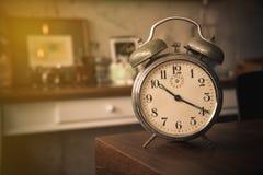 Uhr auf Holztisch mit Weinlesefilter Stockfotografie
