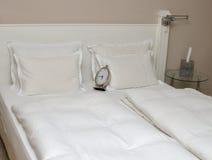 Uhr auf Kissen auf einem Bett Lizenzfreies Stockfoto