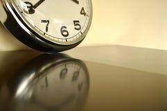 Uhr auf reflektierender Oberfläche Stockfotografie