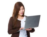 Uhr der jungen Frau auf Notebook Stockfotografie