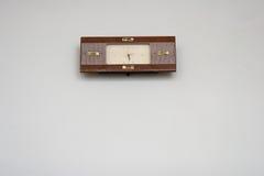 Uhr, die an der weißen Wand hängt Lizenzfreies Stockfoto