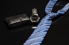 Uhr, Geldbörse und Bindung auf schwarzer Oberfläche mit Reflexion Stockfotografie