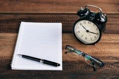 Uhr, Gläser, Stift und leeres Notizbuch auf einem Holztisch Lizenzfreies Stockfoto