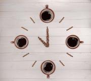 Uhr hergestellt von den Kaffeebohnen und den Schalen auf hölzernem Hintergrund Stockbild
