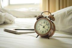 Uhr mit Buch und Bleistift auf Bett Stockbild