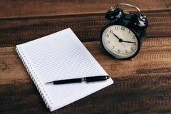 Uhr, Stift und leeres Notizbuch auf Holztischhintergrund Stockfotografie