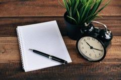 Uhr, Stift und leeres Notizbuch auf Holztischhintergrund Stockbilder