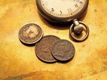 Uhr und alte Münzen Stockfotos