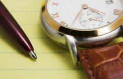 Uhr und Feder auf Kanzleibogenblock Stockbilder